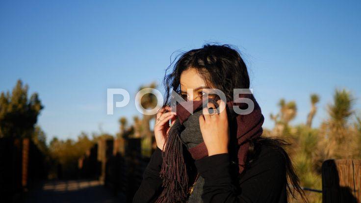 Uma garota gostosa com um lenço vermelho e longos cabelos negros se aquecendo em um resfriado – Stock …