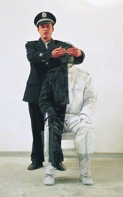Optical illusions: artist Liu Bolin Il s'agit de deux hommes qui posent, un se fait peindre pour l ' insérer ou le fusionner au second homme qui lui théâtrale la scène en mêlant celui qui est peint pour être camouflé à lui.
