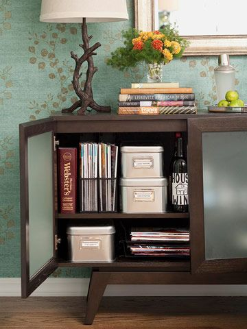 Dual-Purpose Sideboard: If your family room and dining room share a space, put your sideboard to use for both areas as an accent piece and storage unit. Use one half of the cabinet to store books, games, and photo boxes. The other half doubles as a beverage cabinet for barware. Frosted-glass doors cloak the contents.