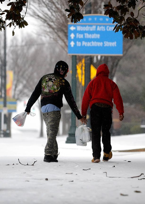 Pedestrians help each other carry groceries on a downtown street as Georgians awake to freezing rain, sleet and snow during a winter storm o...