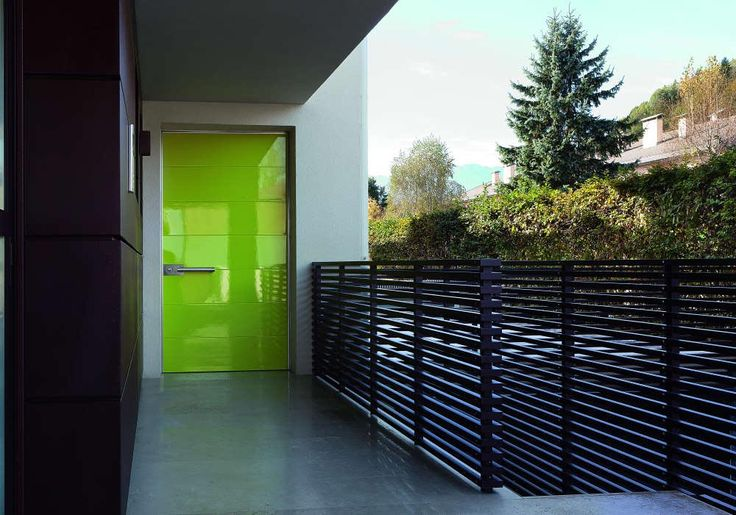 Light green Synua pivot front door by Oikos Venezia in glass.
