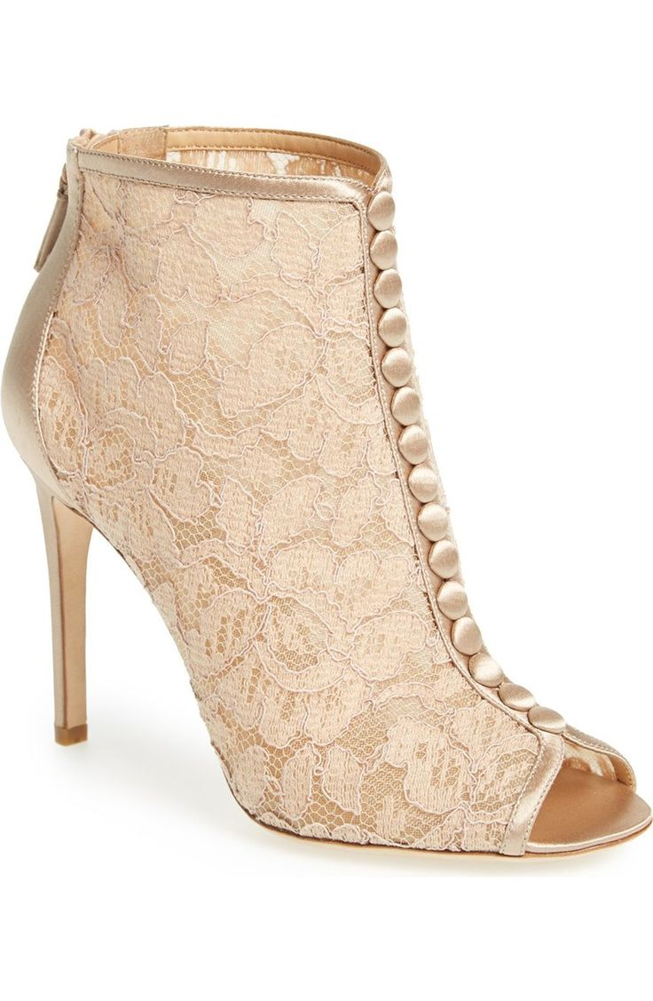 Head over heels for these Victorian-inspired peep toe booties accented with floral lace and faux buttons wrapped in satin.