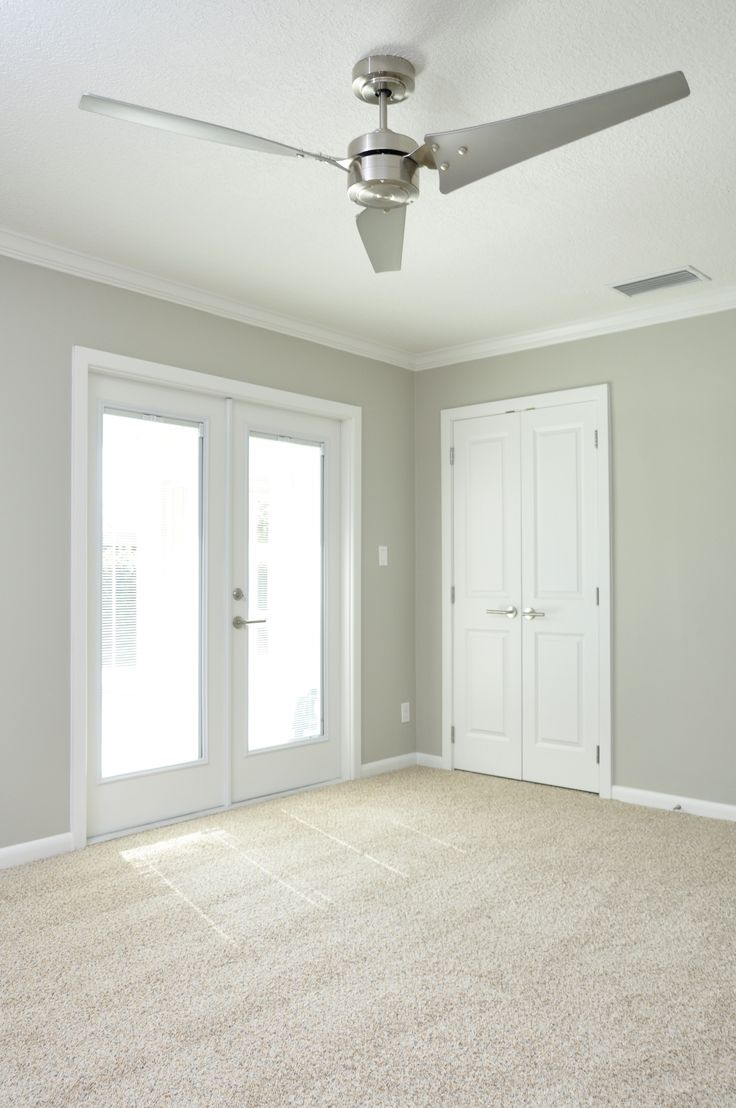 neutral shimmery gray walls with clean white trim double french doors stainless steel three blade modern style fan neutral berber carpet by the best