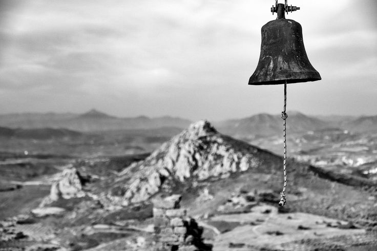 Black and white landscape with a bell hanging above the horizon. The framing of the photo makes the bell appear to be suspended from mid-air.