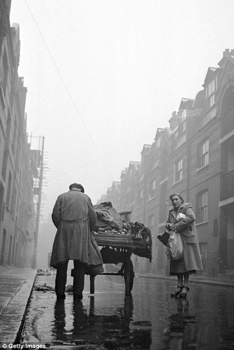 Buying vegetables on a rainy East End day 1952