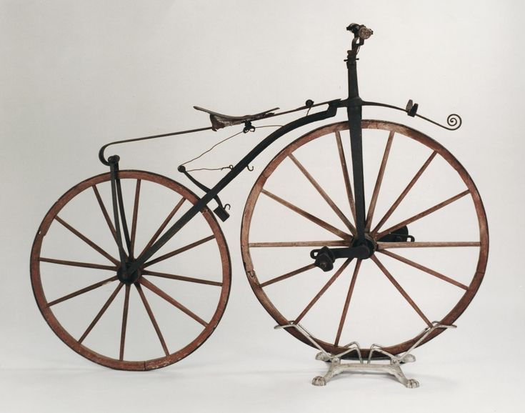 This Velocipede (also known as a 'boneshaker' bicycle), is an early pedal bicycle with an iron frame, wooden wheels with iron rims.The straight handlebars which rotate to operate the spoon brake on the rear wheels and triangular metal pedals which drive the font wheel through cranks. Possibly Scottish, c. 1870