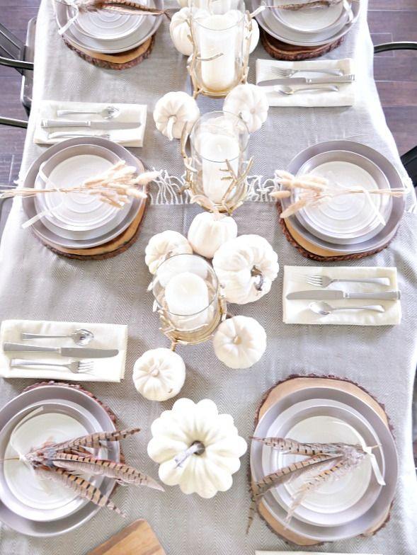 Create an casual elegant fall tables cape using a blanket for a tablecloth and using neutrals with touches of golds and rustic elements
