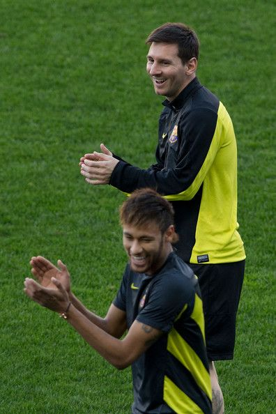 Neymar JR. (L) of FC Barcelona and his teammate Lionel Messi (R) claps joking with their teammates during the training session the day before the UEFA Champions League Quarter-final match between Atletico de Madrid and FC Barcelona at Vicente Calderon Stadium on April 8, 2014 in Madrid, Spain.