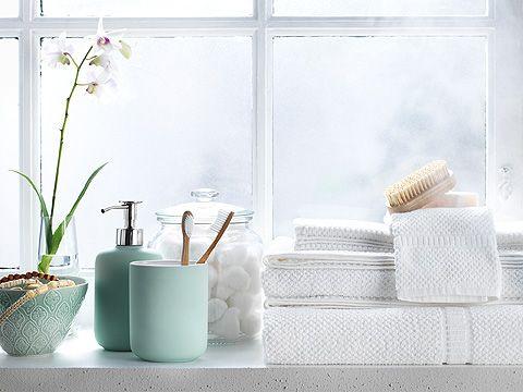 Lysegrøn sæbepumpe, tandbørstekrus og hvide håndklæder ved vindueskarm.