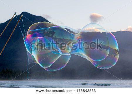 Man making multiple giant soap bubbles on Hanalei beach in Kauai Hawaii