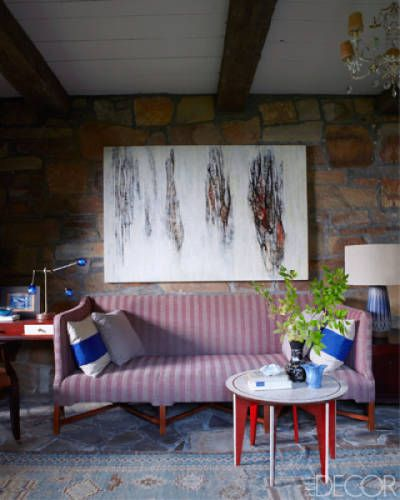 In Holly and Eric Montgomery's Berkshires home, a painting by Holly hangs above a Kaare Klint–inspired sofa by Munder-Skiles in a guest bedroom; the side table is by Nicholas Mongiardo, and the kilim is antique.   - ELLEDecor.com