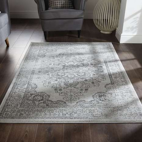 Designed with a damask print in a distressed finish, this charcoal grey rug is completed by an intricately detailed border and features a short pile for high durability.