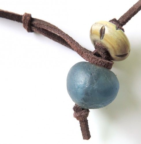 Pendant made of leather, glass, and bone