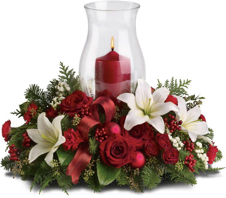 Abeto nobre perfumado e eucalipto semeado são o pano de fundo verde para rosas vermelhas, cravos vermelhos, bagas vermelhas e enfeites vermelho-foscos de Natal. Um recipiente de vidro abriga uma vela vermelha, enquanto fita vermelha com fio acrescenta um toque festivo ao acabamento.  Fotografia: Teleflora.com.