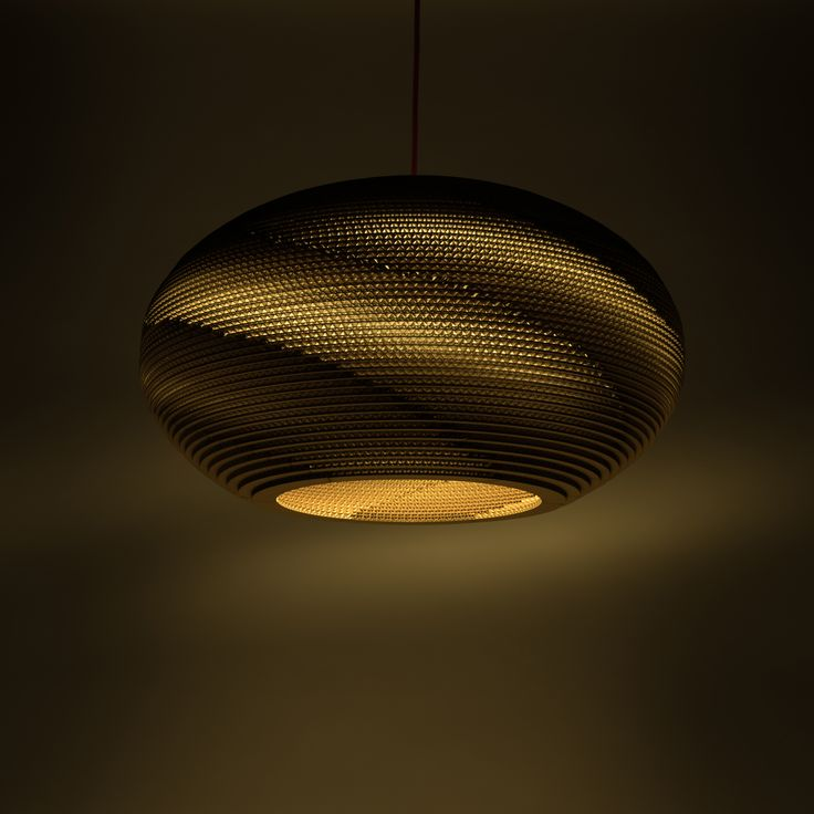 A shade in the shape of a flattened spheroid induces pleasant atmosphere in a living-room or above a dining table. The structure of the cardboard creates an impressive spiral of light around the shade. Choose a pendant cable with the shade to fit your room.
