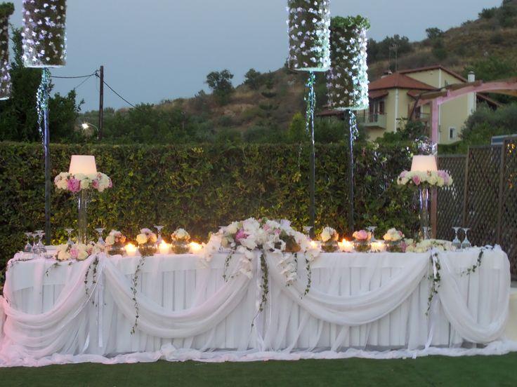 νυφικο τραπεζι , συνθεσεις με κερι ,και μπουκετα απο πεονιες και ορχιδεες, και σκηνικο απο λουλουδενια τοτεμ.