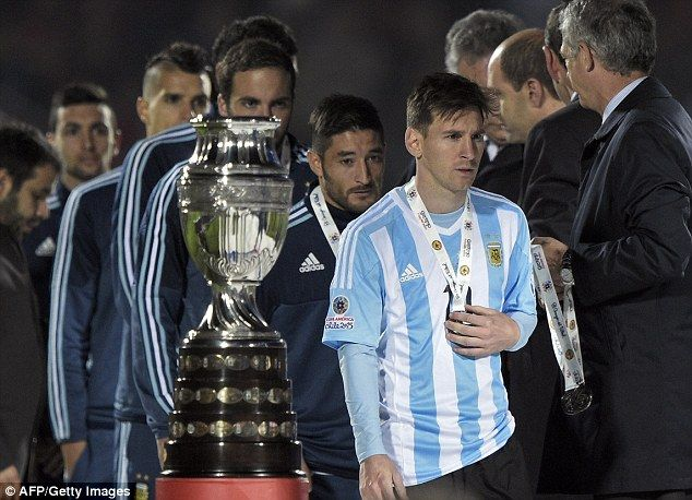 Lionel Messi, whose family were abused during the final, walks past the Copa America trophy