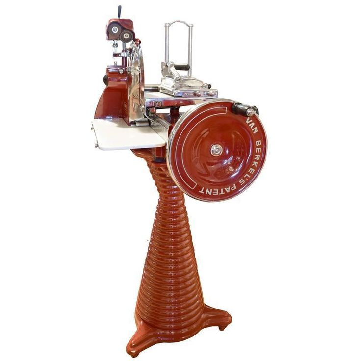 A rare Berkel model 9H prosciutto slicing machine in a red enamel, manufactured in Rotterdam, Netherlands. This smaller scale model, made from 1935-1969, is flywheel operated and features 15 different slicing thicknesses and a blade sharpener and sits atop a ribbed conical base. This slicer has been masterfully restored to excellent working condition.