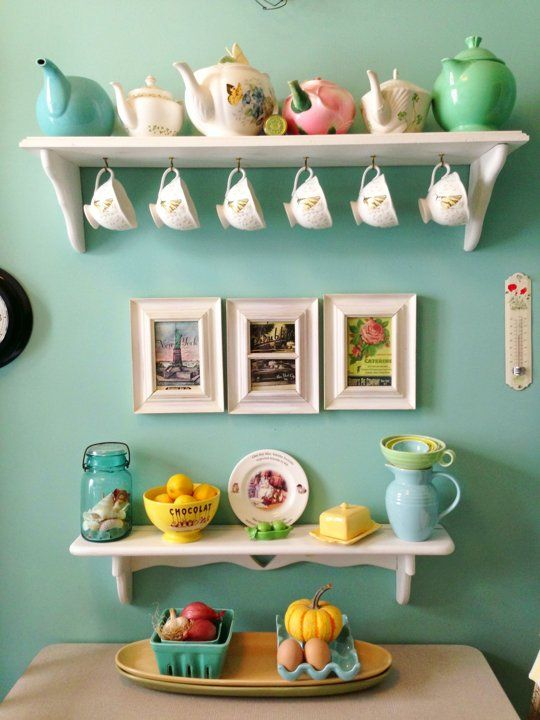 Vintage kitchen styling- colorful teapots against a turquoise aqua wall.
