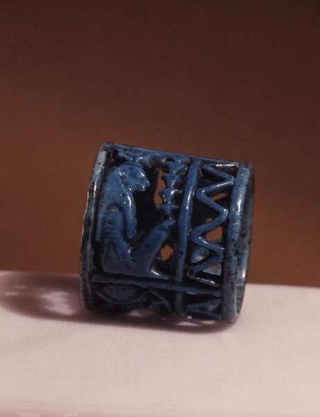Blue faience amuletic finger ring with figures of Thoth,Horus and Isis incorporated in the design, from Tuna el-Gebel Necropolis,2 cm x H 2.3 cm.3rd Intermediate Period,21st-22nd Dynasty.