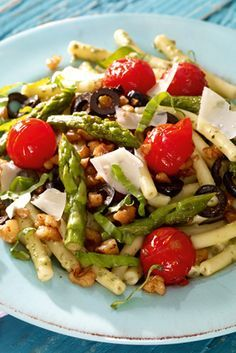 Ein bunter Salat mit Makkaroni, grünem Spargel und Kirschtomaten