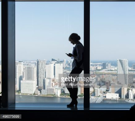 Stock Photo : Silhouette of woman using mobile phone in city.