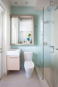 Really good use of space in a super tiny bathroom with a petite vanity and shower that is built into tiled floor and straight glass door.