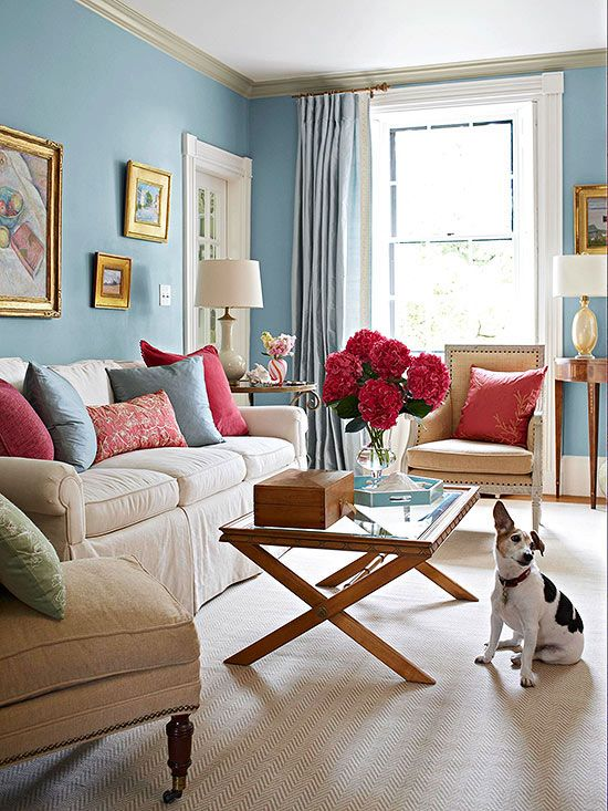 The neutral furniture and rug in this powder blue room prevent the color palette from being too overwhelming, and allows the bright magenta to tie everything together.