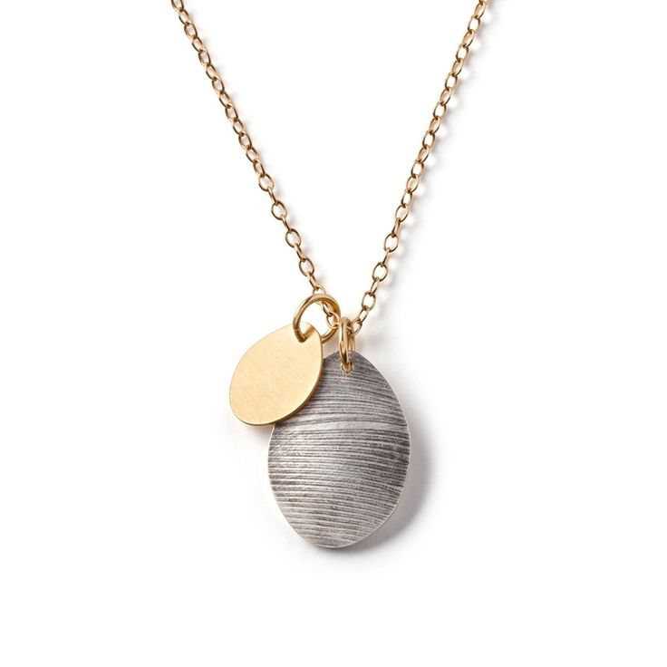 Feathered Egg Necklace by Diane Dorsey. Handbuilt in 925 sterling silver, the 'egg' shape while elegant and simple, varies slightly with each bird and is the inspiration for this pendant. Add the texture of a found raven feather and oxidized patina on an 18kt gold chain, and you have a very organic jewel.