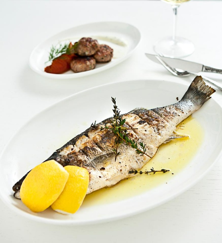 lavraki whole mediterranean sea bass served with fresh herbs lemon and olive oil