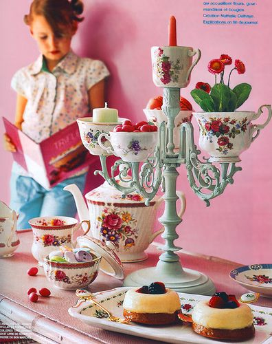 Tea cups on a painted candelabra - a lovely centerpiece.