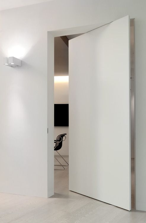 L'Invisible white pivoting frameless door.