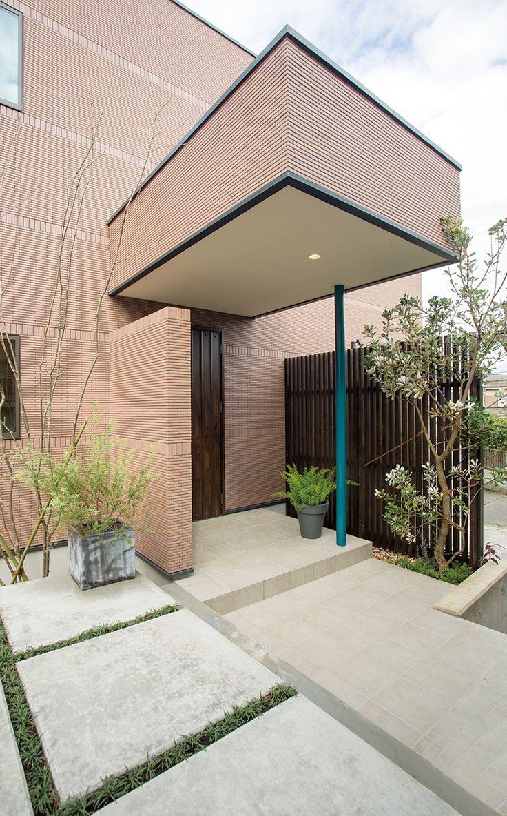 重厚感あふれる総タイル貼りの玄関ポーチ。雨どいをデザインした青い柱がアクセントです。|デザイン|ナチュラル|タイル|