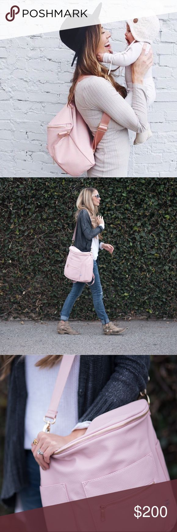 """❤️FAWN DESIGN Blush Backpack❤️ I have many of these so I'm just trying to recoup my $- I love in Utah where this company is located so I had to pay tax. NO TRADES!  We say diaper bag, but they make great anytime bags. Wear your bag as a backpack or messenger bag! Inside can be pulled out for easy cleaning-Outside and inside are fully wipeable faux leather. Total of 10 pockets; 4 outside, 6 inside including a zipper pocket.  13"""" high x 15"""" wide x 8"""" deep Messenger Strap is 51"""" at longest…"""