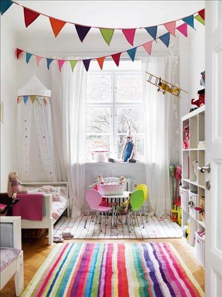 De två tuftade ullmattorna är mysiga att gräva ner tårna i, den färgglatt randiga mattan närmast i bild är Strib från Ikea. Mattan med alfabetet, abc, är formgiven av Karin Mannerstål och kommer från Kateha. Sängarna är utdragssängar, Vikare, 152–206cm, och den öppna förvaringen är hyllan Expedit, allt från Ikea. Korgarna i facken gör det lätt att hålla reda på leksakerna. Heddas sänghimmel kommer från Ikea och vimplarna från Sprall. Stolar vid pysselhörnan samt svamplampa från R.o .o.m…