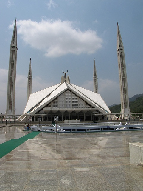 The Faisal Mosque is the largest mosque in Pakistan, located in the national capital city of Islamabad. Completed in 1986, it was designed by Turkish architect Vedat Dalokay to be shaped like a desert Bedouin's tent.  It is situated at the north end of Faisal Avenue, putting it at the northernmost end of the city and at the foot of Margalla Hills, the westernmost foothills of the Himalayas. It is located on an elevated area of land against a picturesque backdrop of the Margalla Hills.