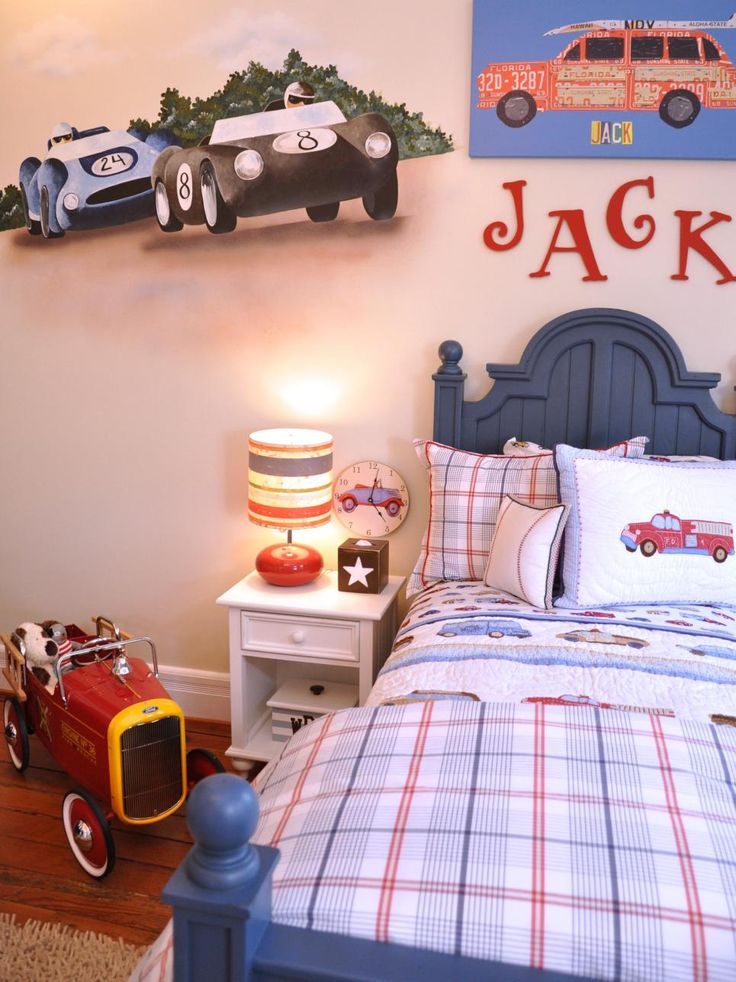 This bedroom features a car theme, including a painted mural of two race cars, a painting of a red car, car-themed bed linens and a car-themed clock. Above the bed, red letters are used to spell the boy's name.