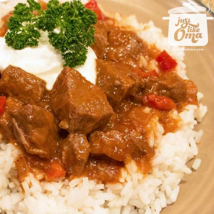 Plate of rice topped with German goulash cooked in a slow cooker. Garnished with sour cream and parsley.
