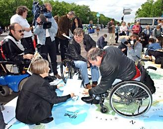 Der 5. Mai: viele Aktionen, ein Ziel  Junge und alte Menschen an einem Aktionsstand    Auf die Situation von Menschen mit Behinderung in Deutschland aufmerksam machen und sich dafür einsetzen, dass alle Menschen gleichberechtigt an der Gesellschaft teilhaben können: Das ist das Ziel des Europäischen Protesttags zur Gleichstellung von Menschen mit Behinderung.