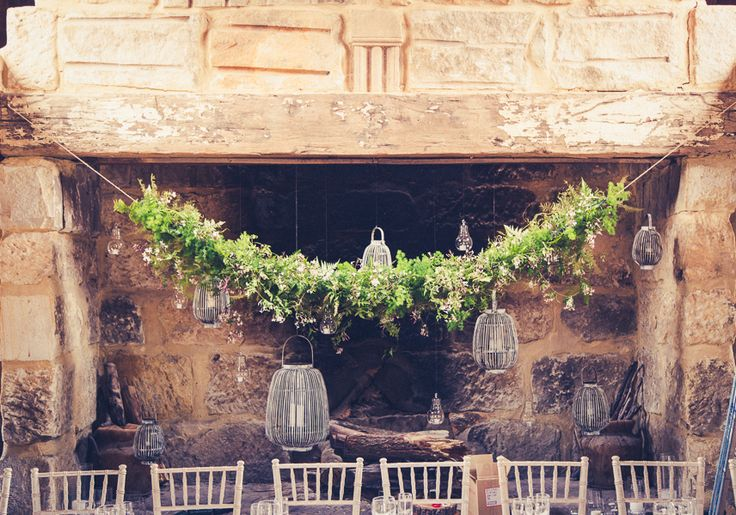 A foliage garland filled with greenery including jasmine and fern hung above the beautiful rustic fireplace at the wedding reception venue.