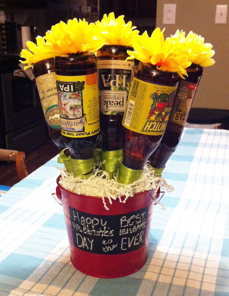 "Valentine's Gift for Men - Beer Bouquet ""Beerquet""   1.  Hot glue dowel rods to beer bottles & secure with ribbon.    2.  Hot glue fake flowers onto bottom of beer bottles.  3.  Put floral foam in bottom of pail.  Stick dowels into the floral foam to secure the beer flowers in the foam.  4. Decorate pail and fill with basket filler fluff."