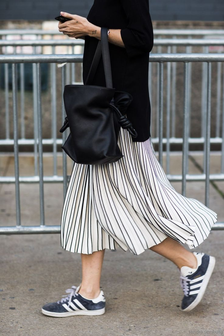 Adidas kicks with a graphic pleated skirt and leather bucket bag.