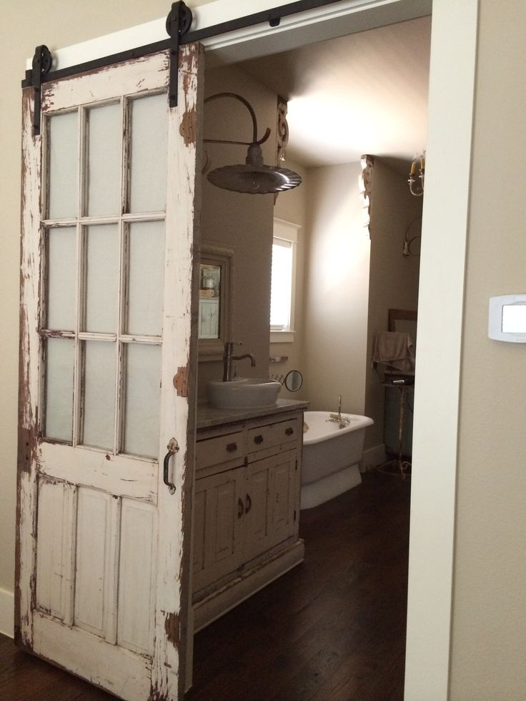 Old, chippy, distressed door turned barn door style setup...with matching colored vanity.