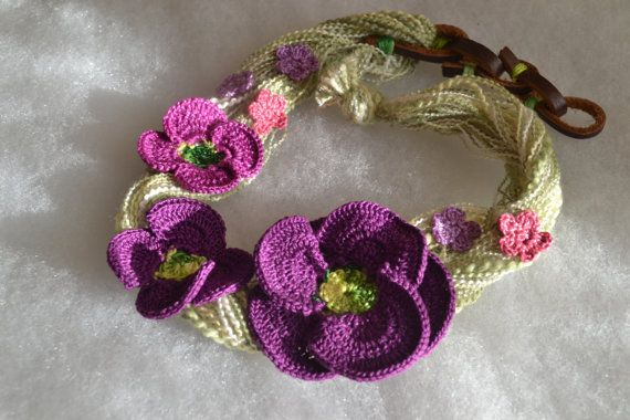 This is a lovely asymmetrical necklace with crocheted from cotton thread beautiful poppies in purple and lilac shades. Embellished with brown genuine leather closure. Size: approx. 51.0 cm (20 1/4) long,  large poppy is 6.5 cm (2 1/2) in diameter,  smaller poppies are 5 cm (2) in diameter, small flowers are 1.8 cm (3/4) in diameter.  You might also like http://www.etsy.com/shop/FlowersbyIrene?section_id=6816630