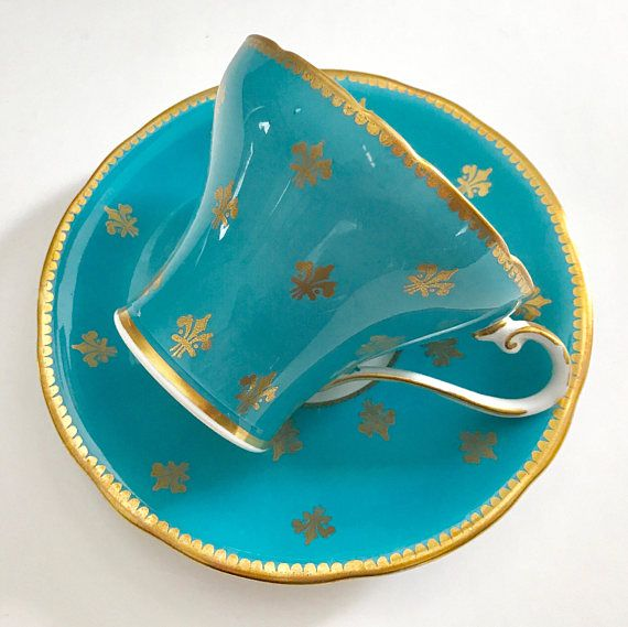 Beautiful vintage Aynsley tea cup and saucer, turquoise outside, white on the inside with a large pink rose, with small gold Fleur De Lise details on both cup and saucer. It is in good condition, both pieces ring nicely, no chips, cracks or crazing. There are a couple of small