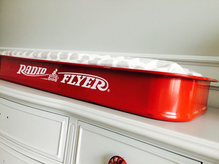 Red wagon changing station on gray painted dresser. Vintage boy nursery.