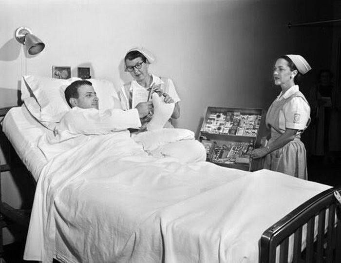 #The Good Samaritan Hospital Ladies Auxiliary are visiting a patient in his hospital bed. They are bringing amusements candy and cigarettes. The nurse is helping him hold a current Readers Digest. Photo by Clyde Putnam Jr. Ca. 1955. Portland Oregon [700 x 539] #history #retro #vintage #dh #HistoryPorn http://ift.tt/2fwQep1