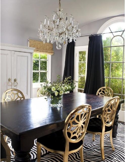 Gold dining chairs with a black dining room table and a black and white stripe