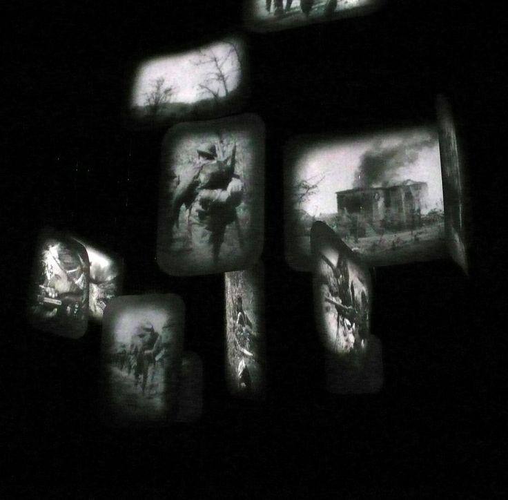 """Frame-David Loom / In una stanza completamente nera, un flusso circolare di immagini a partire da foto d'archivio che ripercorrono, come in un film della memoria, i drammatici 145 giorni di permanenza e stazionamento del fronte sul fiume Senio. A liberazione avvenuta Cotignola è un cumulo di macerie, un paese """"blasted of the map""""."""