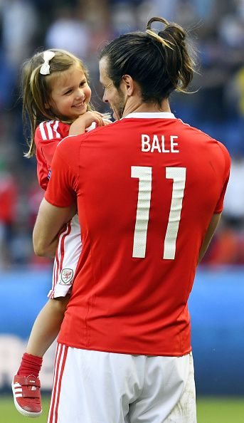 #EURO2016 Wales' forward Gareth Bale holds his daughter Alba Viola as he acknowledges the crowds following the team's 10 win in the Euro 2016 round of sixteen...